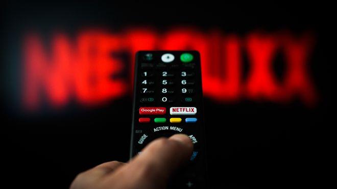 Pantalla con el fondo de Netflix, persona tomando el control remoto