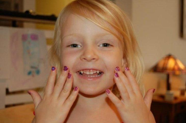 Niña con las uñas pintadas