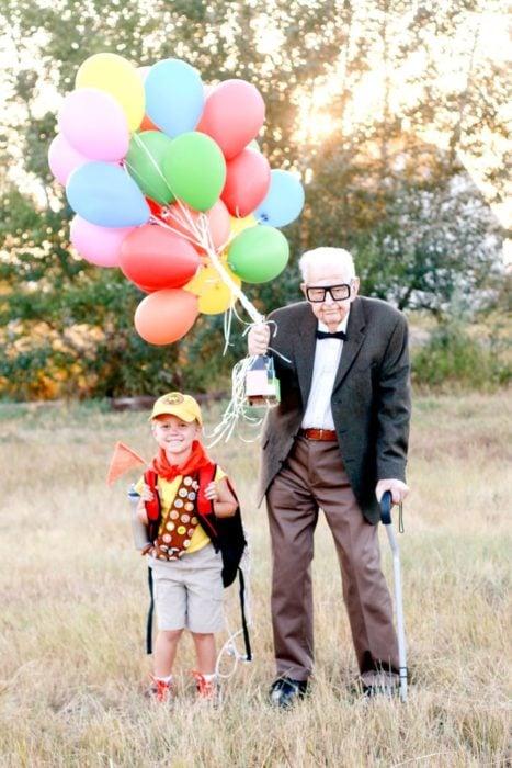 Fotografía de Rachel Perma inspirada en Up, película Disney, niño y abuelo disfrazados, sisteniendo una hilera de globos