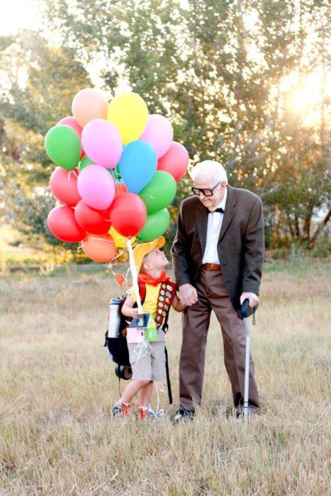 Fotografía de Rachel Perma inspirada en Up, película Disney, niño y abuelo tomados de la mano, soteniendo una hilera de globos mirándose a los ojos