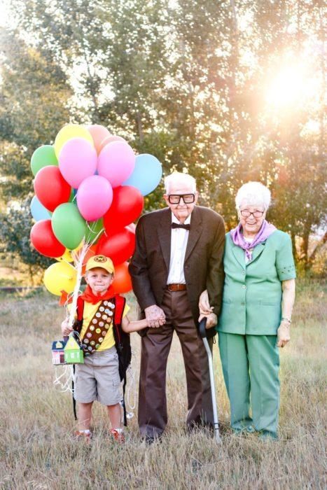Fotografía de Rachel Perma inspirada en Up, película Disney, pareja de abuelos y su nieto tomados de la mano, sonriendo para una foto instantánea
