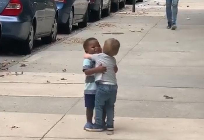 Niños de dos años en la acera de la calle abrazándose