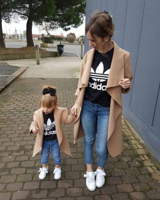 Madre e hija llevando abrigo en tono camel, jeans de mezclilla azul, tenis blancos y blusas negras