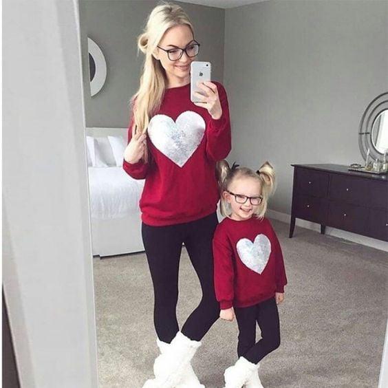 Madre e hija con outfits similares en sudadera roja decorada con un corazón y un pantalón oscuro