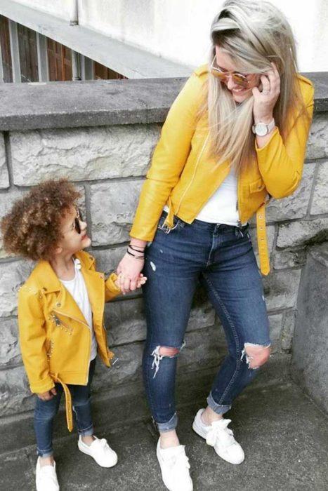 Madre e hija usando chaquetas amarillas de cuero con jeans de mezclilla y camisas blancas