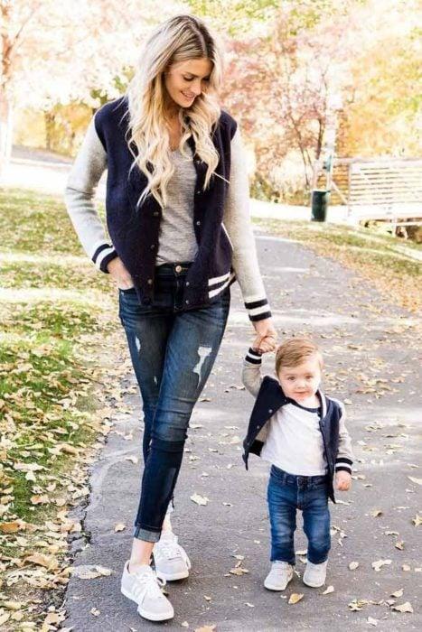 Madre e hijo tomados de las manos con jeans de mezclilla, sudaderas deportivas