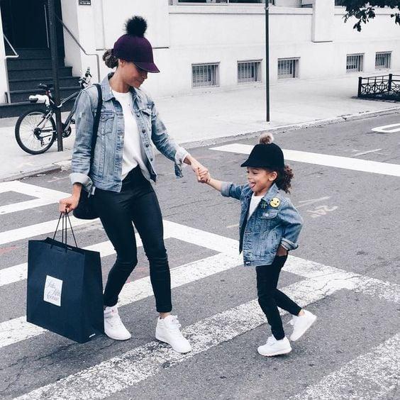 Madre e hija usando outfits similares con camisas blancas, jeans oscuros y chaqueta de mezclilla azul cielo