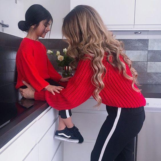 Madre e hija con pants deposrtivos en negro y suéteres rojos de estambres