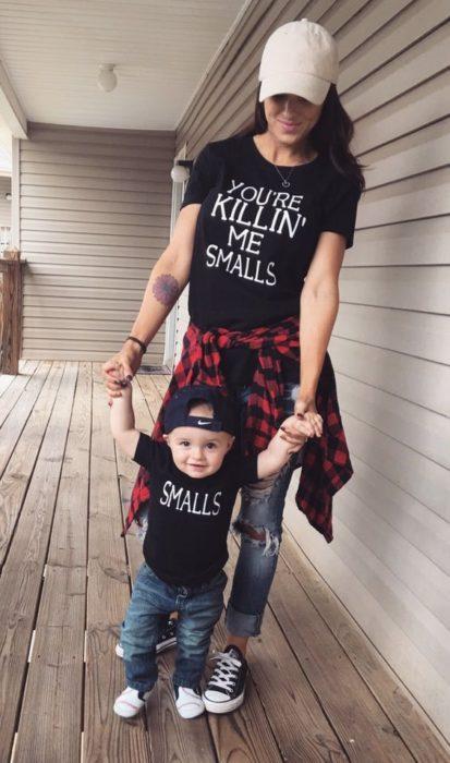 Madre e hijo usando playeras oscuras con jeans negros y cachuchas oscuras