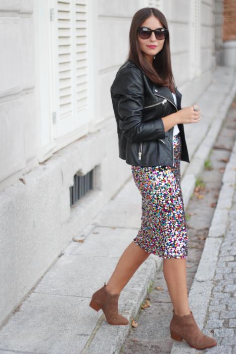 Chica usando una falda larga con estampado de colores, botines café y chaqueta de cuero