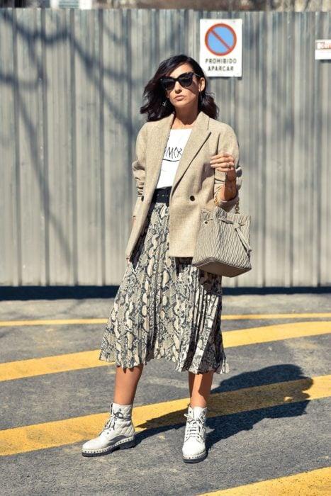 Chica usando una falda animal print, saco, botines y blusa de color blanco