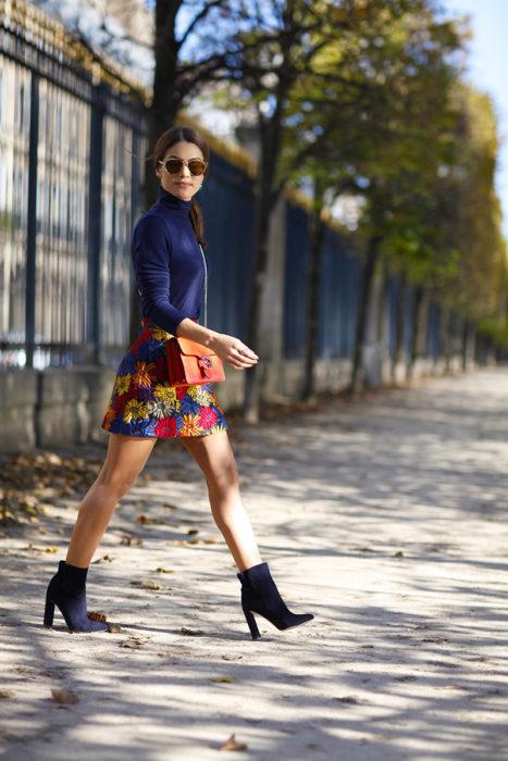 Chica usando una falda de estampado floral, botines y chaqueta de color azul