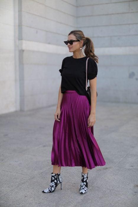 Chica usando una falda de color morado, sueter de color negro y botines estampados