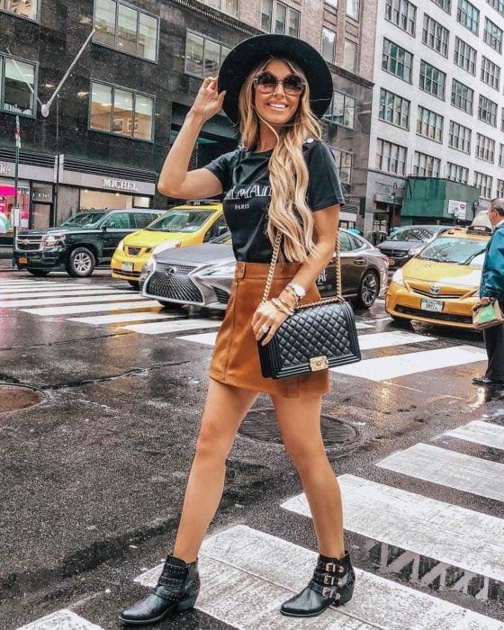 Chica usando una falda de color café botines, sombrero y camisa de color negro