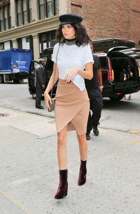 Kendall Jenner caminando por las calles de Nueva York usando una falda de color café, botines negros y blusa blanca