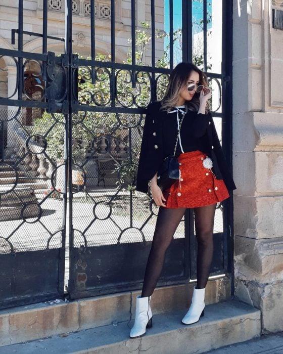 Chica parada frente a una puerta posando para una foto mientras usa una blusa negra, falda de color rojo y botines blancos