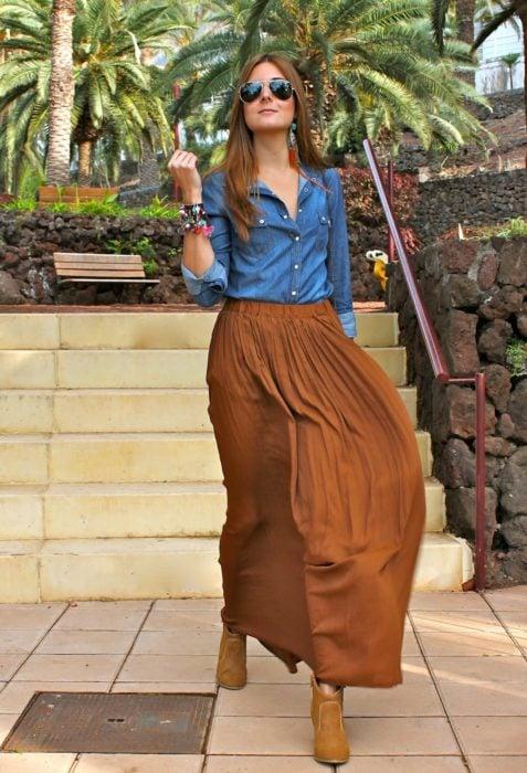 Chica usando una falda de color café, blusa de color azul mezclilla y botines de color café