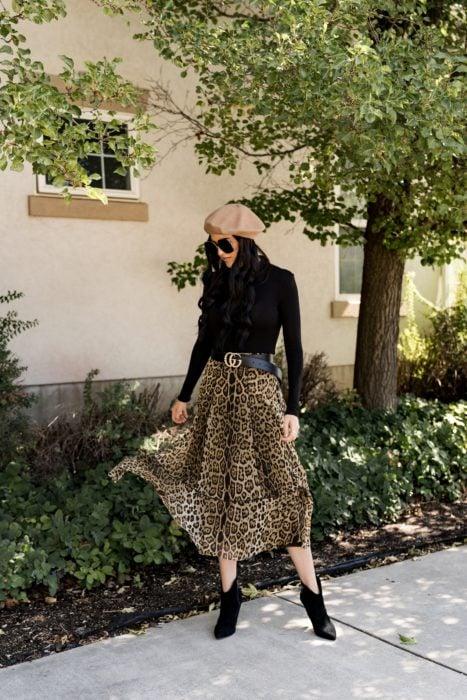 Chica usando una falda animal print, blusa negra, botines y sombrero de felpa