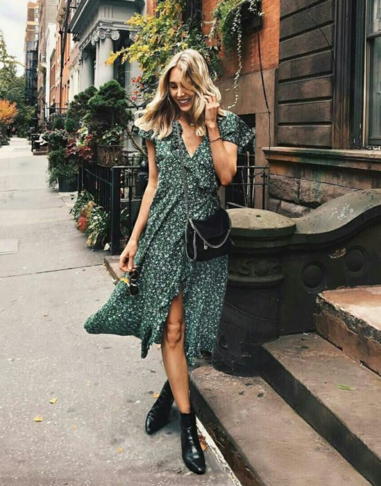 Outfits para otoño; mujer rubia posando para foto en la calle, con vestido floreado verde y botines negros