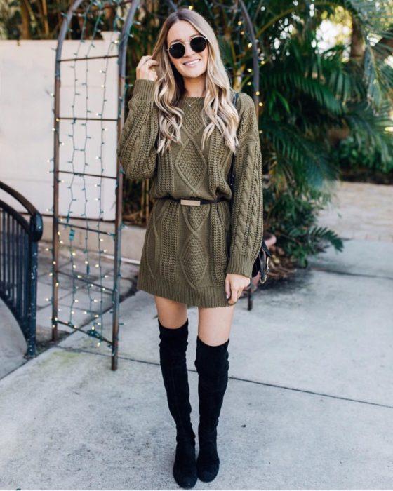 Outfits para otoño; chica usando suéter oversized verde estilo abuelita como vestido con cinto delgado y botas negras largas