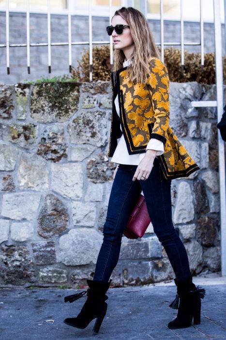 Outfits para otoño; mujer de cabello rubio balayage, con saco floreado amarillo, jeans y botines negros