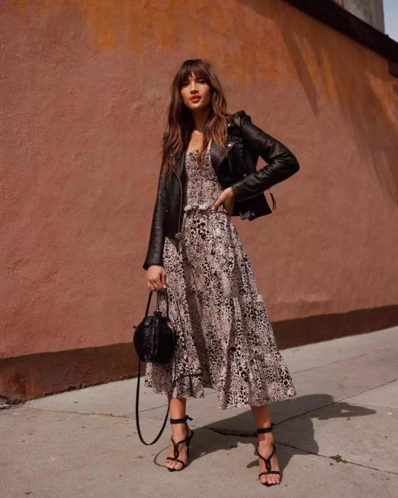 Outfits para otoño; chica con vestido de animal print y chaqueta de cuero negra, con sandalias de tacón