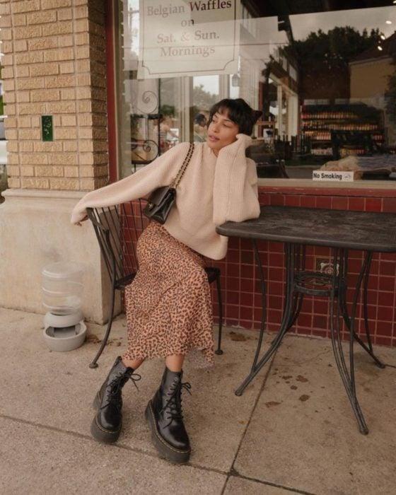 Outfits para otoño; chica con estilo vintage, suéter oversized beige, falda larga de animal print, botas Dr. Martens