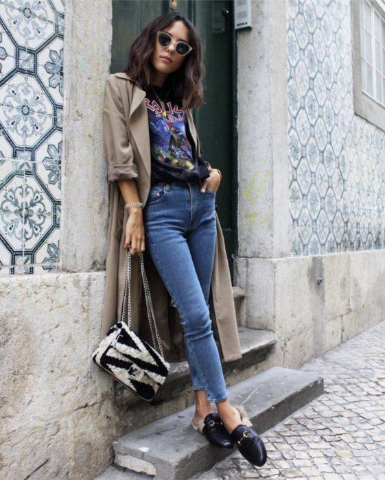Outfits para otoño; foto de chica en escaleras, con camisa de bandas de rock, mom jean y saco largo caqui