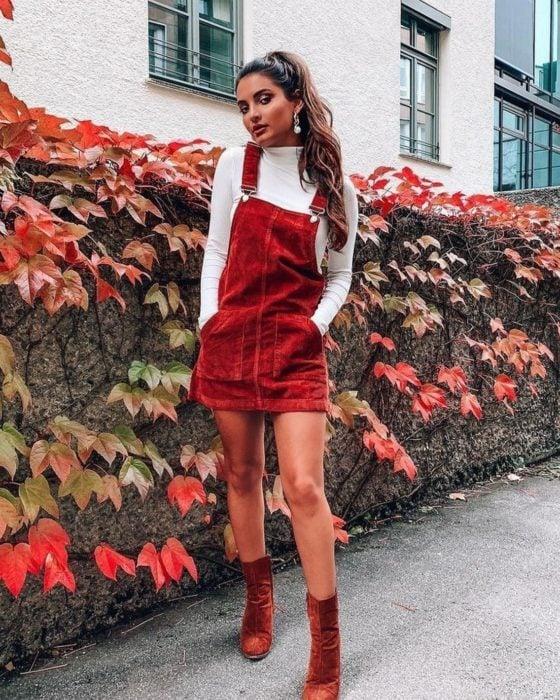 Outfits para otoño; chica de cabello castaño con peinado de coleta de caballo, con overol rojo de pana sobre blusa blanca de manga larga y cuello de tortuga, con botines rojos
