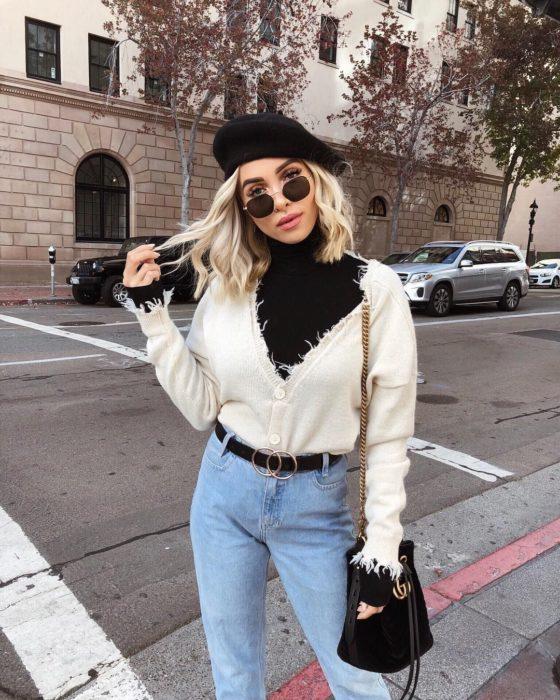 Outfits para otoño; chica rubia de cabello bob a los hombros, con boina estilo francesa, suéter deshilachado y mom jeans