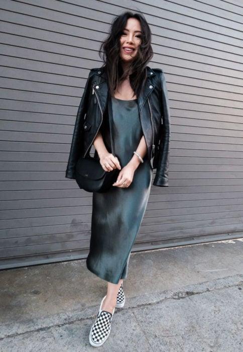 Outfits para otoño; chica de ojos rasgados con vestido de seda negro con chaqueta de cuero y tenis vans con cuadros