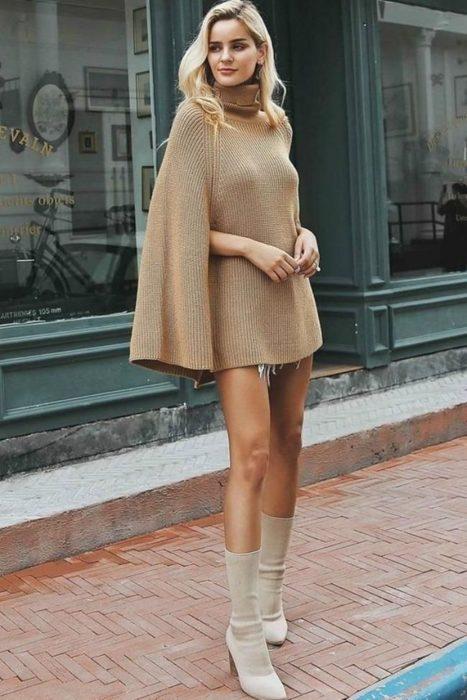 Outfits para otoño; mujer rubia con chalina beige oversized con cuello de tortuga y botas color marfil medianas