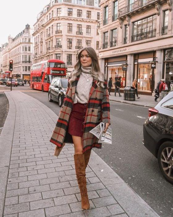 Outfits para otoño; chica de cabello platinado caminando en la calle con suéter de cuello de tortuga, abrigo de cuadros, falda de pana y botas cafés largas
