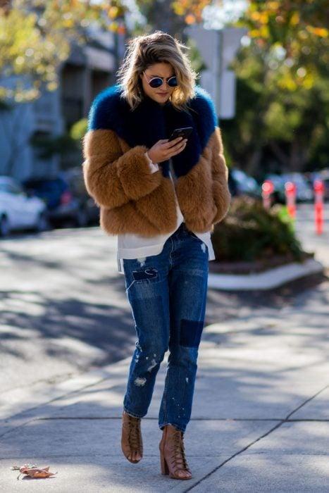 Outfits para otoño; mujer mirando su celular, con abrigo afelpado azul y café, con mom jeans y lentes grandes y redondos