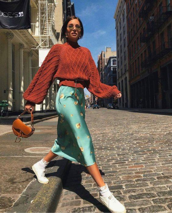 Outfits para otoño; chica cruzando la calle empedrada, con suéter oversized de abuelita, color anaranjado y falda de satín verde menta floreada, con tenis blancos