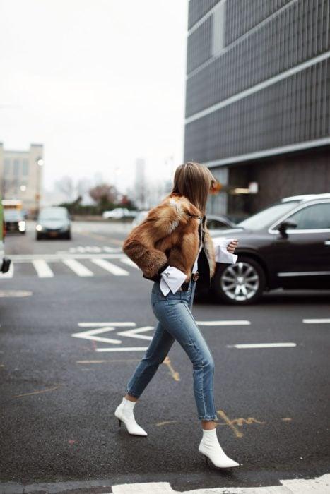 Outfits para otoño; mujer cruzando la calle con abrigo peludo café, jeans azules y botines blancos