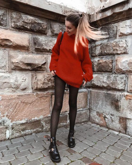 Outfits para otoño; chica con peinado de cola de cabello alta, con suéter oversized rojo usado como vestido, con medias de puntos y botines de trabajo con hebillas