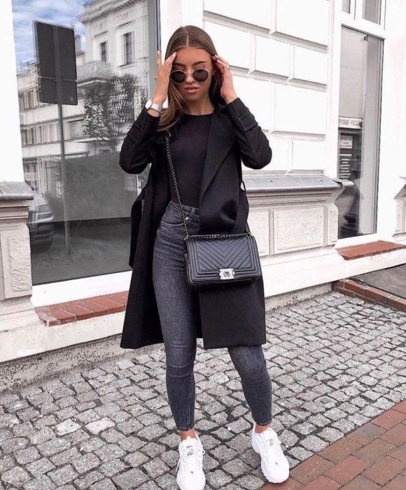 Chica usando un pantalón de color gris, top negro y abrigo