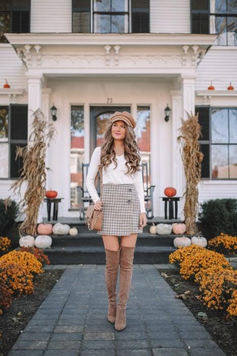 Chica usando una falda de color café, botas altas y sombrero