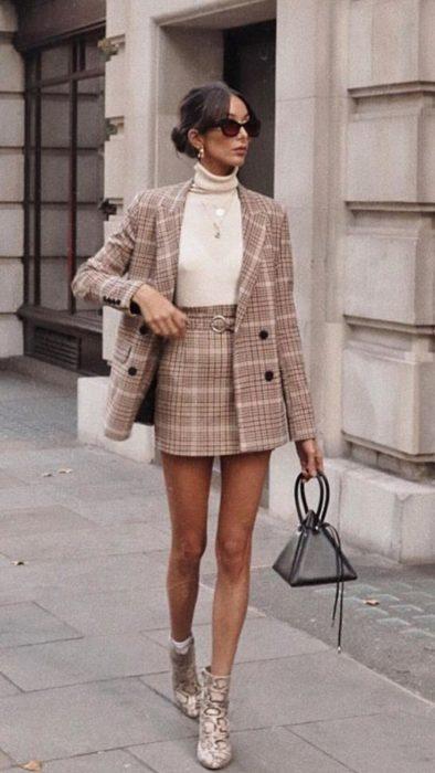 Chica usando un traje de falda a cuadros con botines de color café