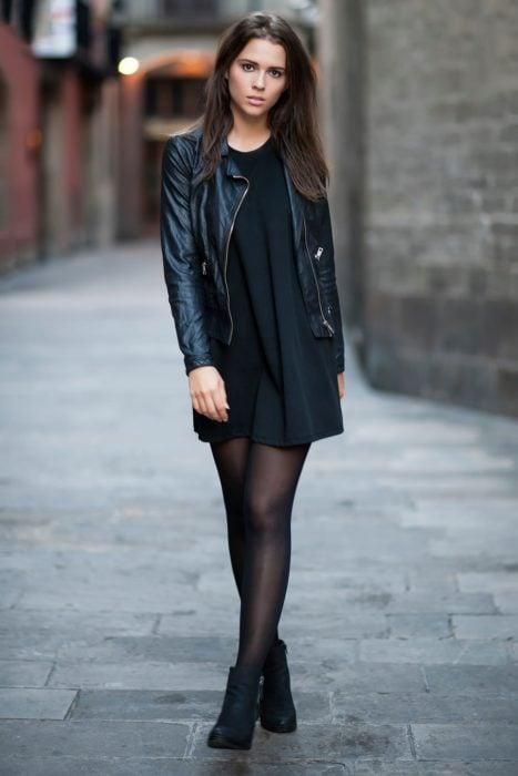 Chica usando botines, medias, vestido y chaquetas de color negro