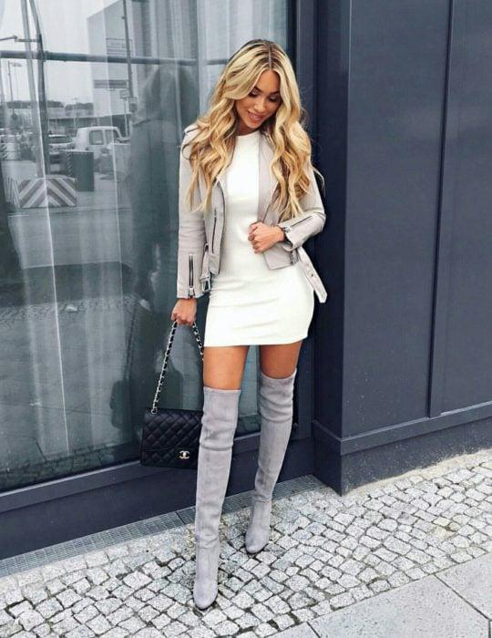 Chica usando un vestido de color beige, chaqueta y botas de color gris