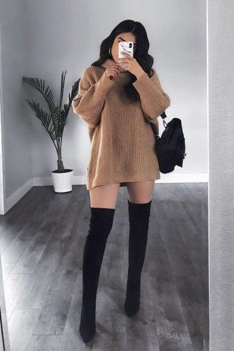 Chica usando un vestido estilo suéter de color café con botas altas de color negro