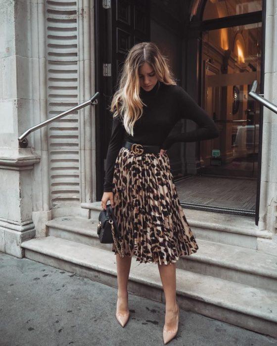 Chica usando una falda animal print, sueter de color negro y botines