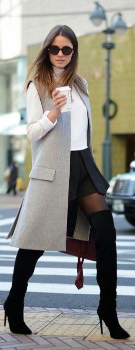Chica usando un abrigo largo, falda y botas largas
