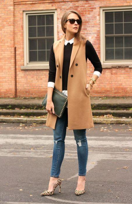 Chica usando un chaleco largo, jeans y zapatos de tacón
