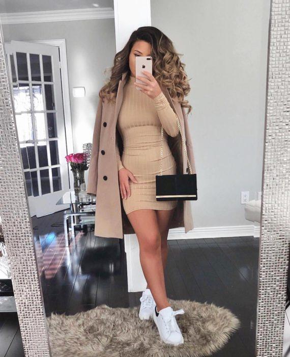 Chica usando un vestido pegado al cuerpo, tenis y abrigo largo de color café