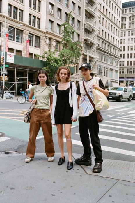 Estudiantes de Parsons y New School muestran sus atuendos para su primer día de clases; tres amigos en la calle vestidos a la moda con pantalones anchos cafés, vestido sencillo negro y playera con zapatos de plataforma