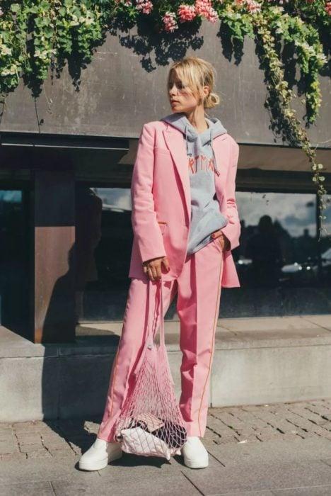 Chica usando un traje corte sastre en color rosa y con una sudadera debajo del saco