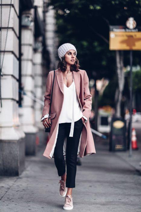 Chica caminando por la calle mientras usa unos jeans negros, blusa blanca, boina y saco rosa